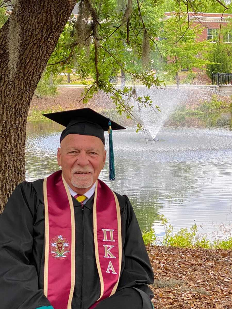 An older college graduate in cap and gown