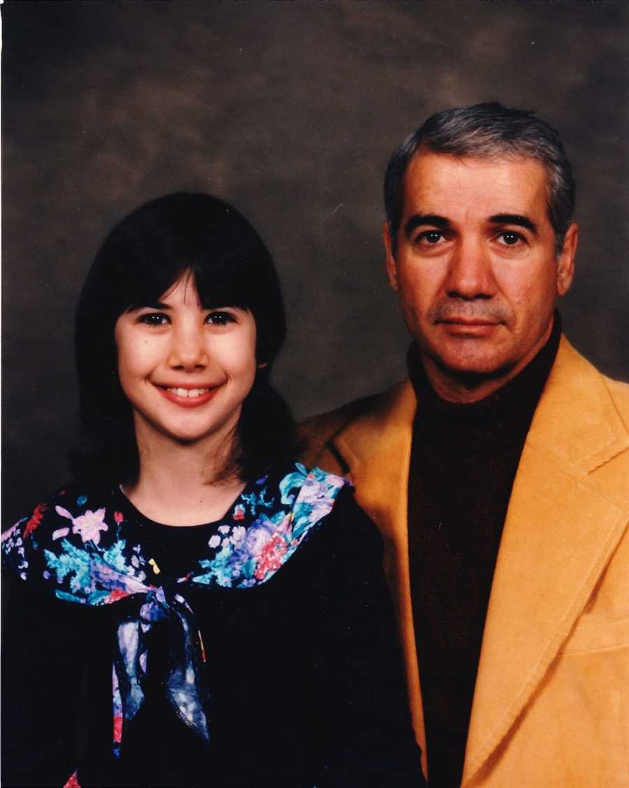 Young girl smiling with her father, not smiling