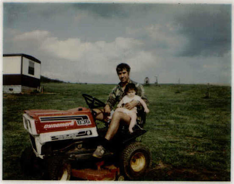 Dad on riding lawnmower holding young daughter