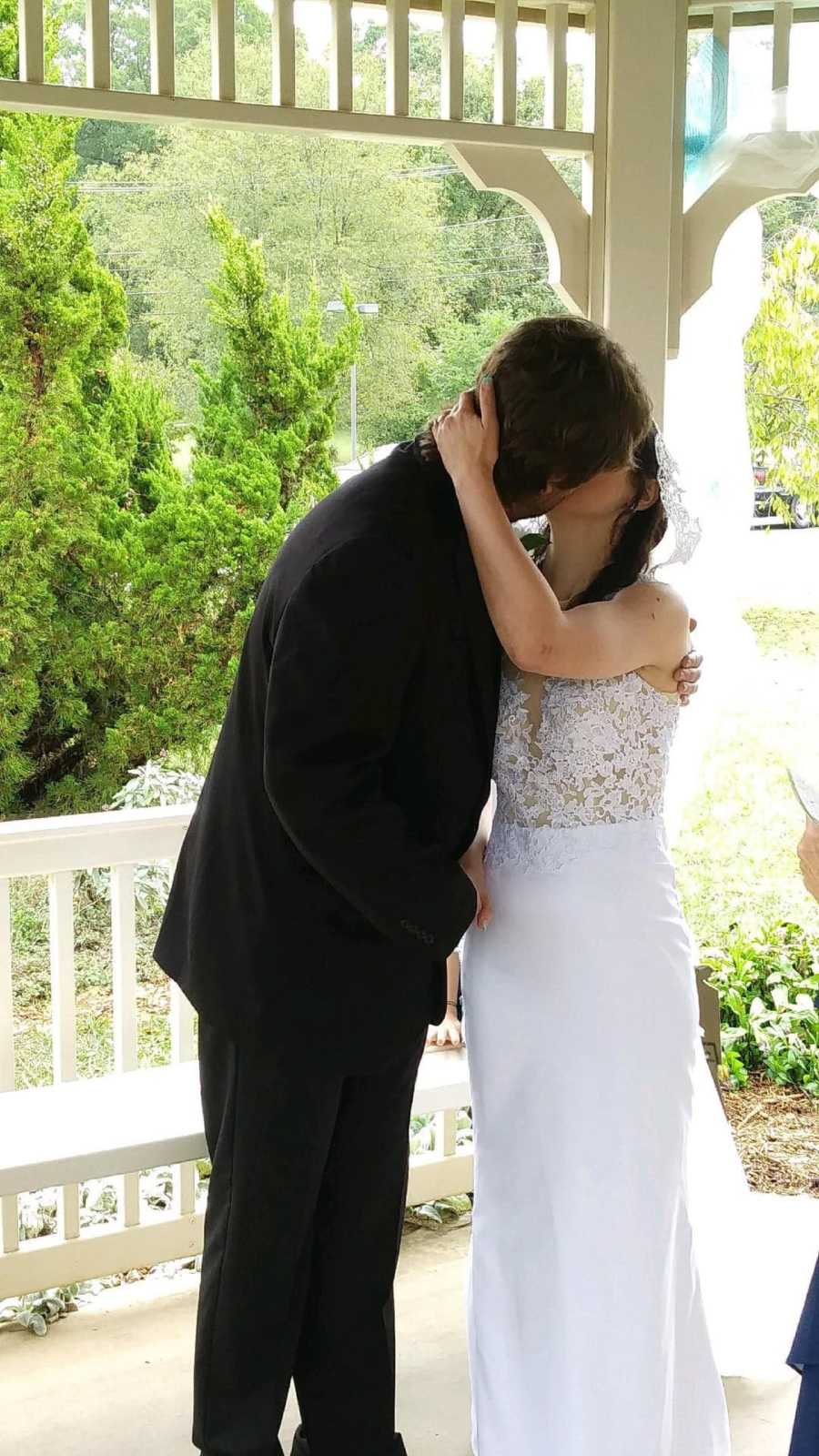 Young bride in wedding dress kissing young groom in suit