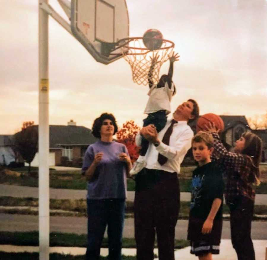 An adoptive father holds up his daughter to shoot a basketball
