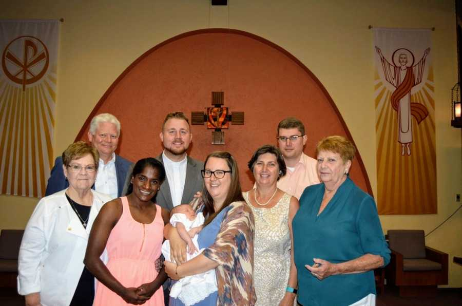 An Indian transracial adoptee stands with her family in a church