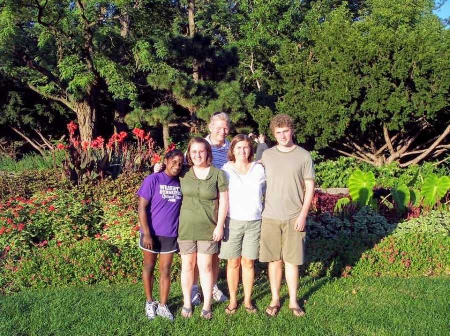 An Indian transracial adoptee and her family stand toegther outdoors