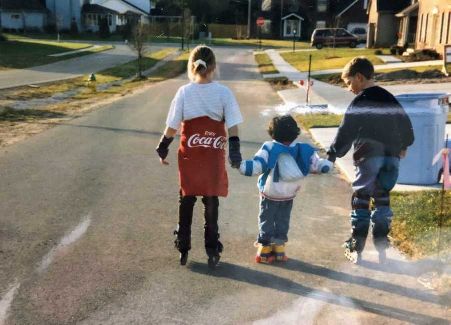 A pair of siblings teach their adopted sister how to roller blade