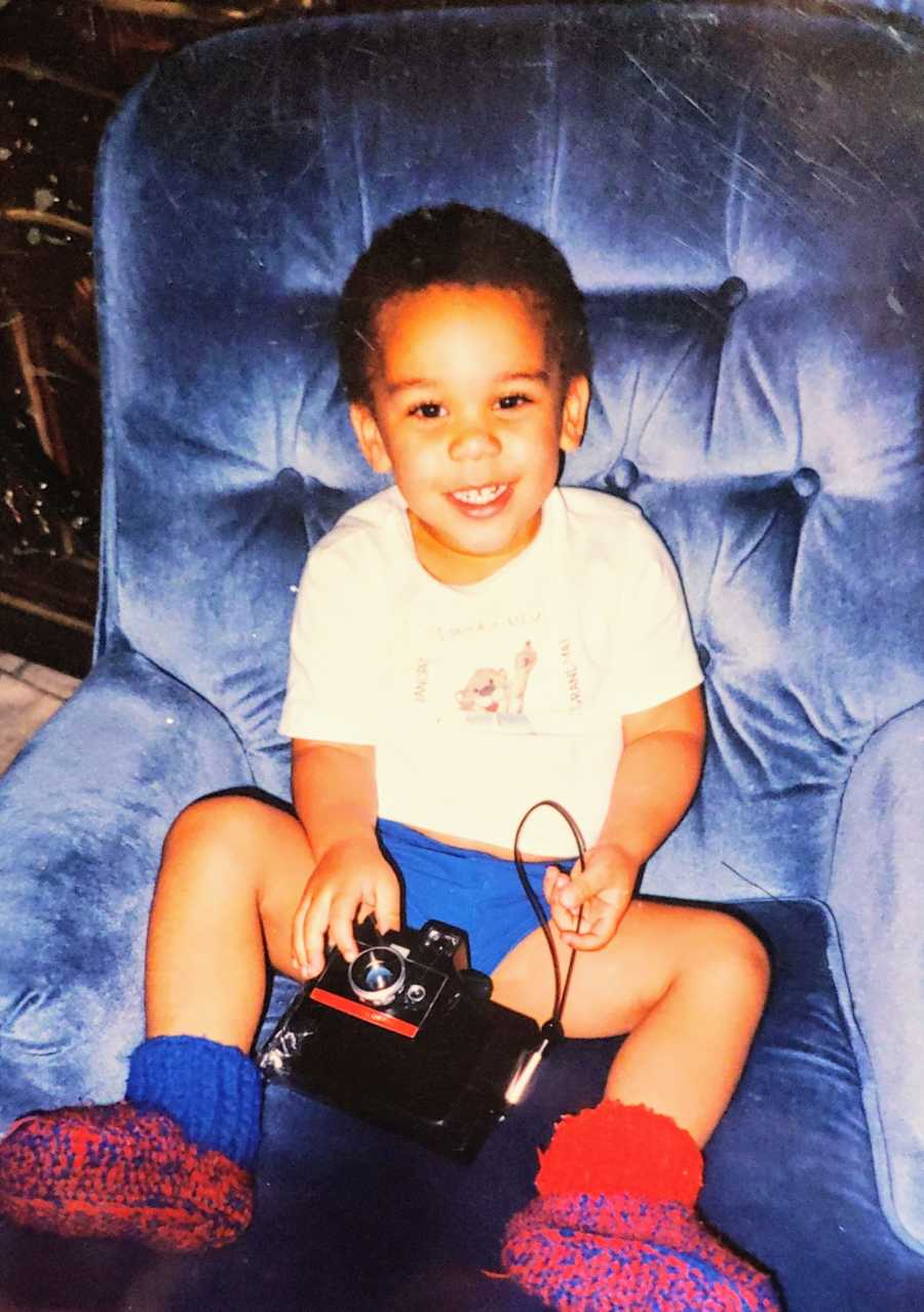 A mixed race adopted boy sits on a blue chair holding a camera