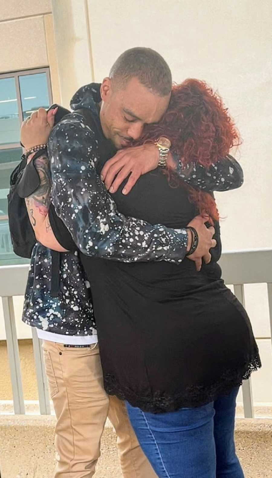 An adult adoptee hugs his birth mother in an airport