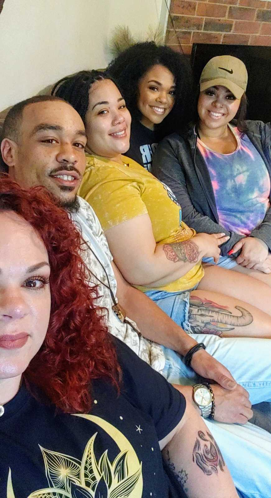 An adoptee with his birth mother and biological sisters on a couch