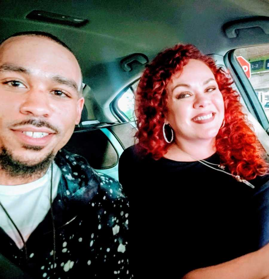 An adult adoptee and his mother sit together in a car