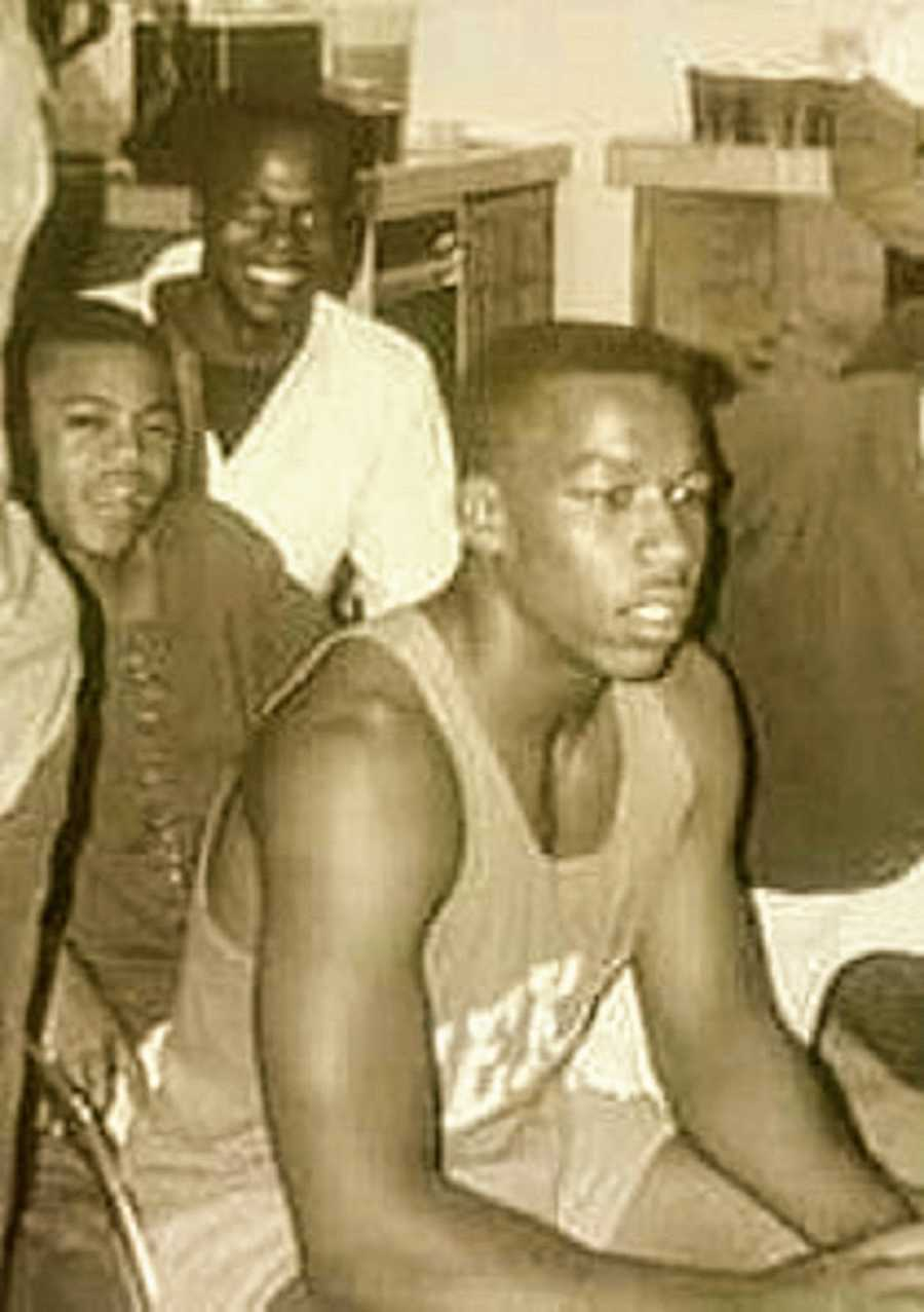A Black teenager sits with others in a sports uniform