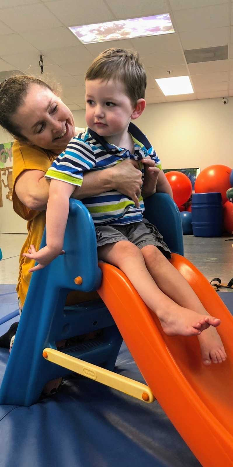 A mom and her son with special needs on a slide