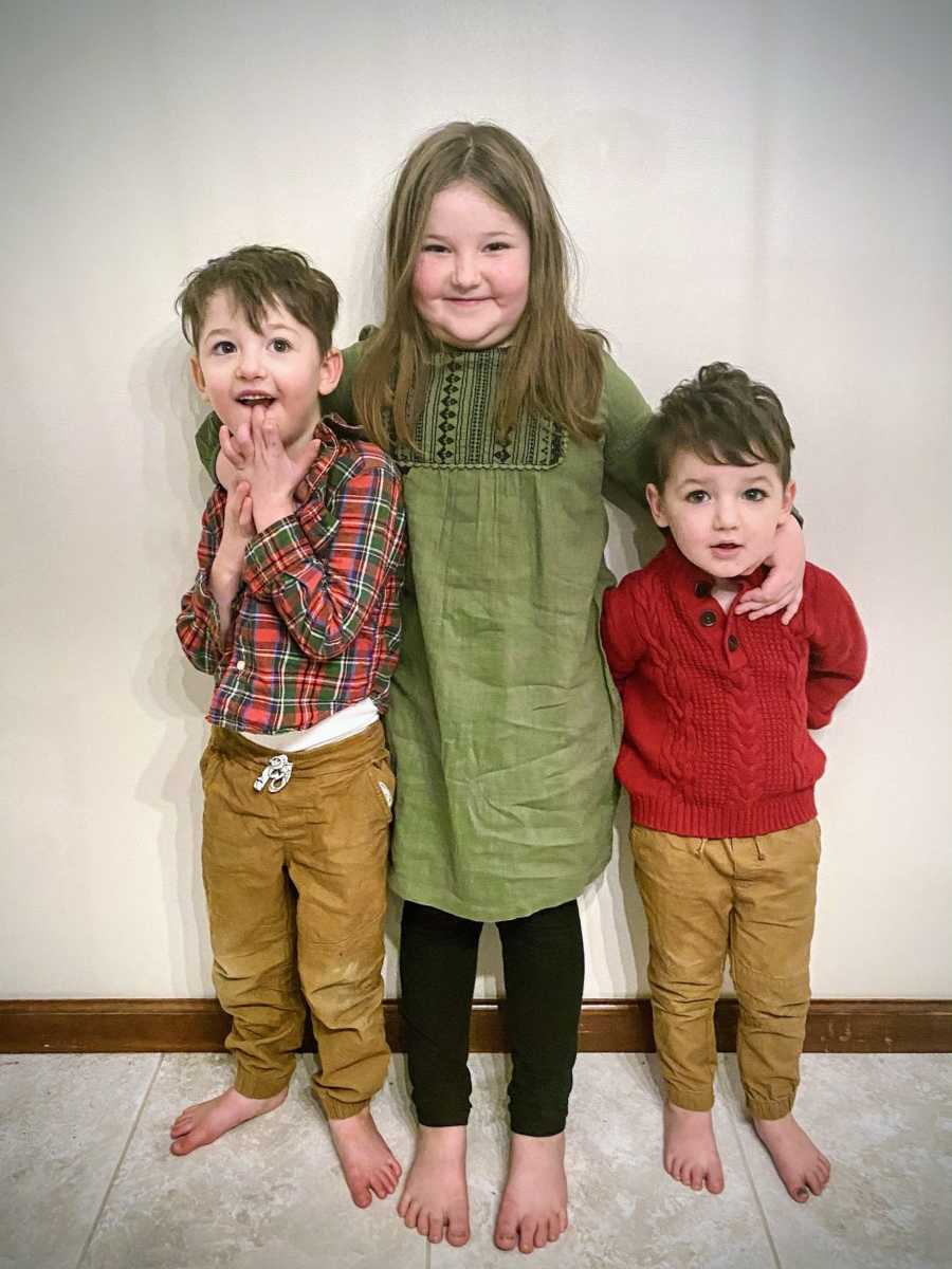 A boy with special needs stands with his brother and sister