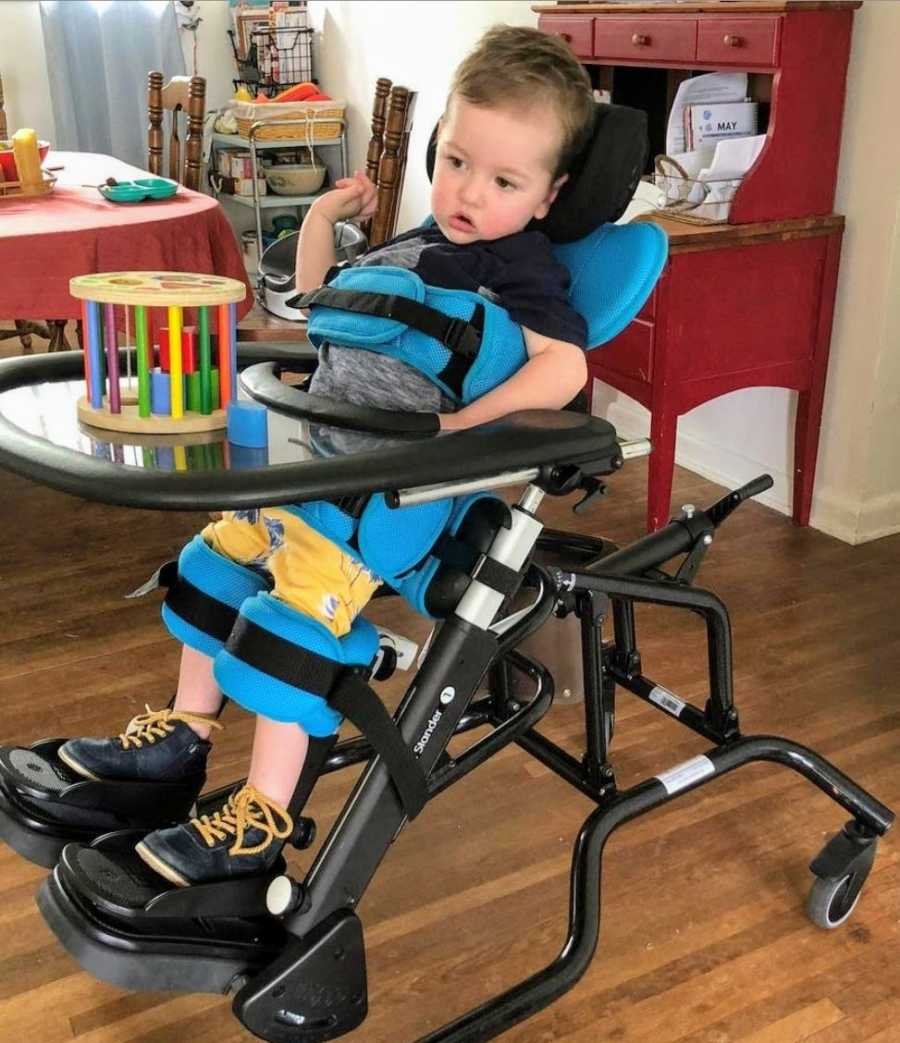 A 2-year-old boy in a vertical wheelchair