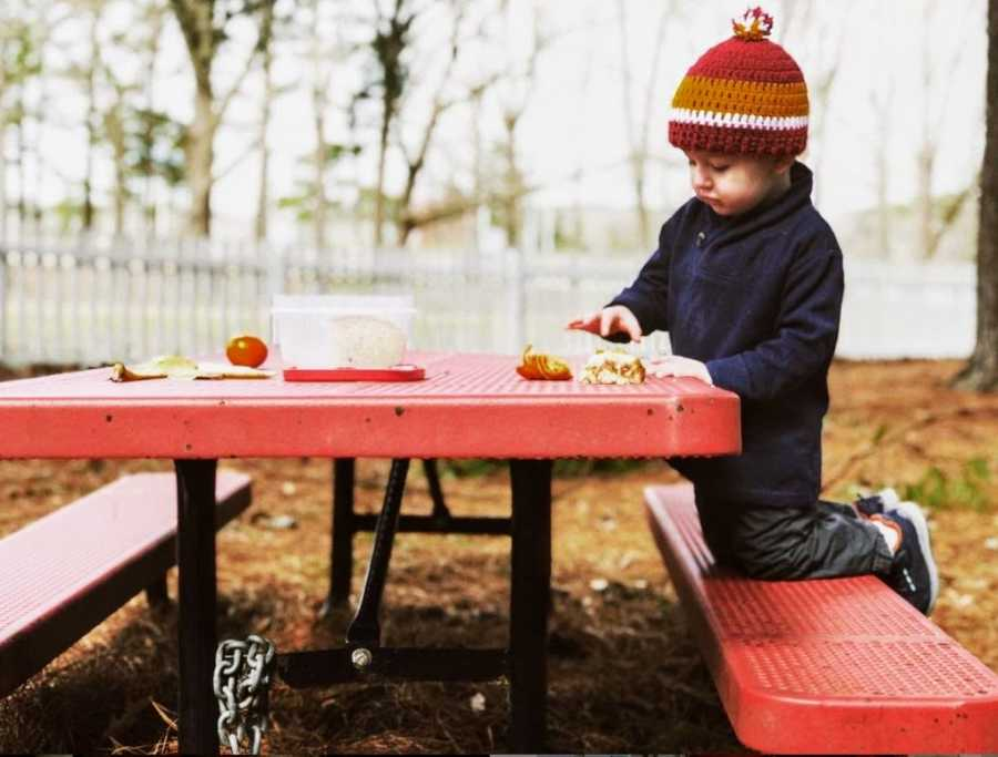 A two-year-old boy sits at a picnic table wearing a hat