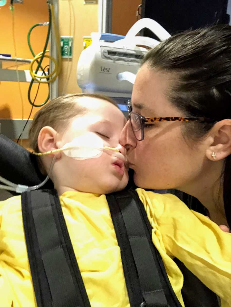 A boy wearing a breathing tube is kissed by his mother