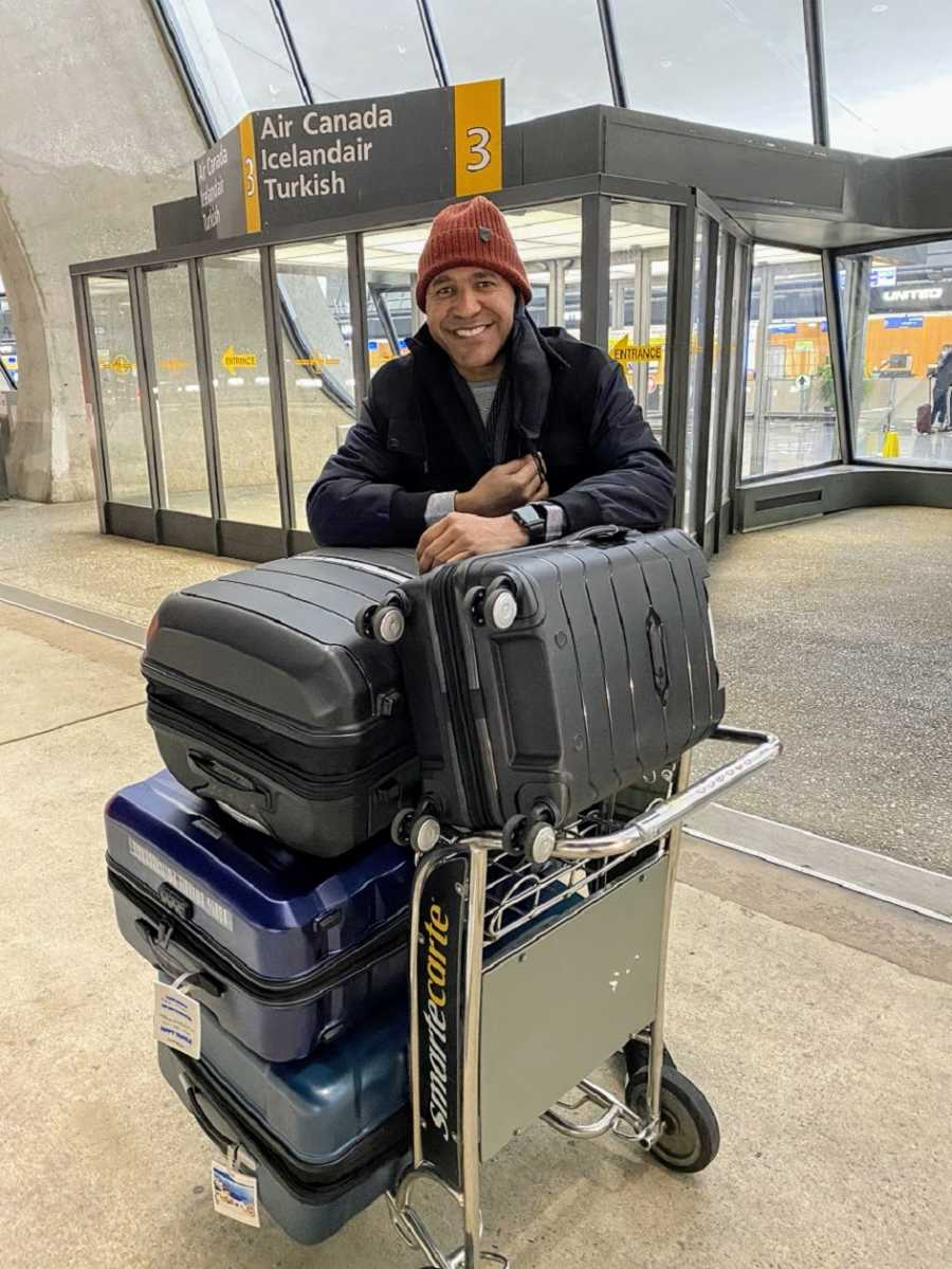 A man stands in an airport with a large pile of luggage