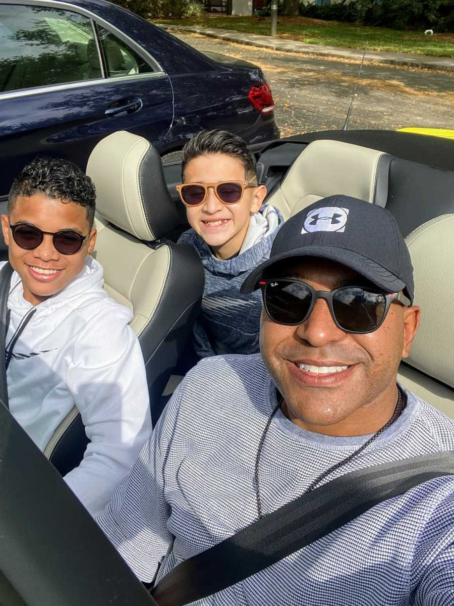 A single adoptive father sits with his sons in a convertible