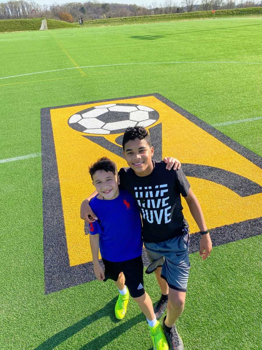 A pair of brothers stand together on a soccer field