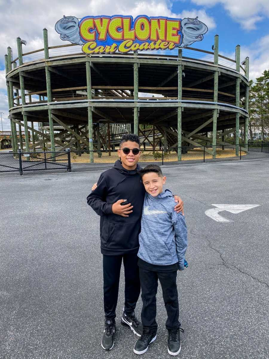 A pair of brothers stand outside a rollercoaster