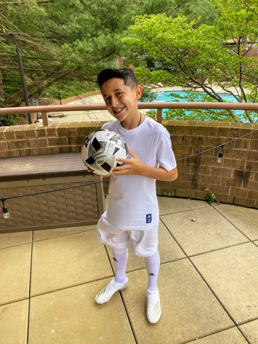 An adopted boy holds a soccer ball on an outdoor deck