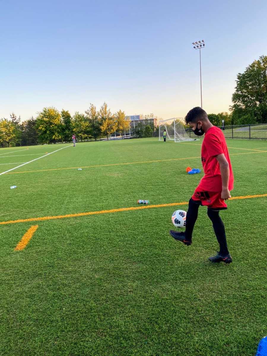 An adopted boy wearing red kicks a soccer ball