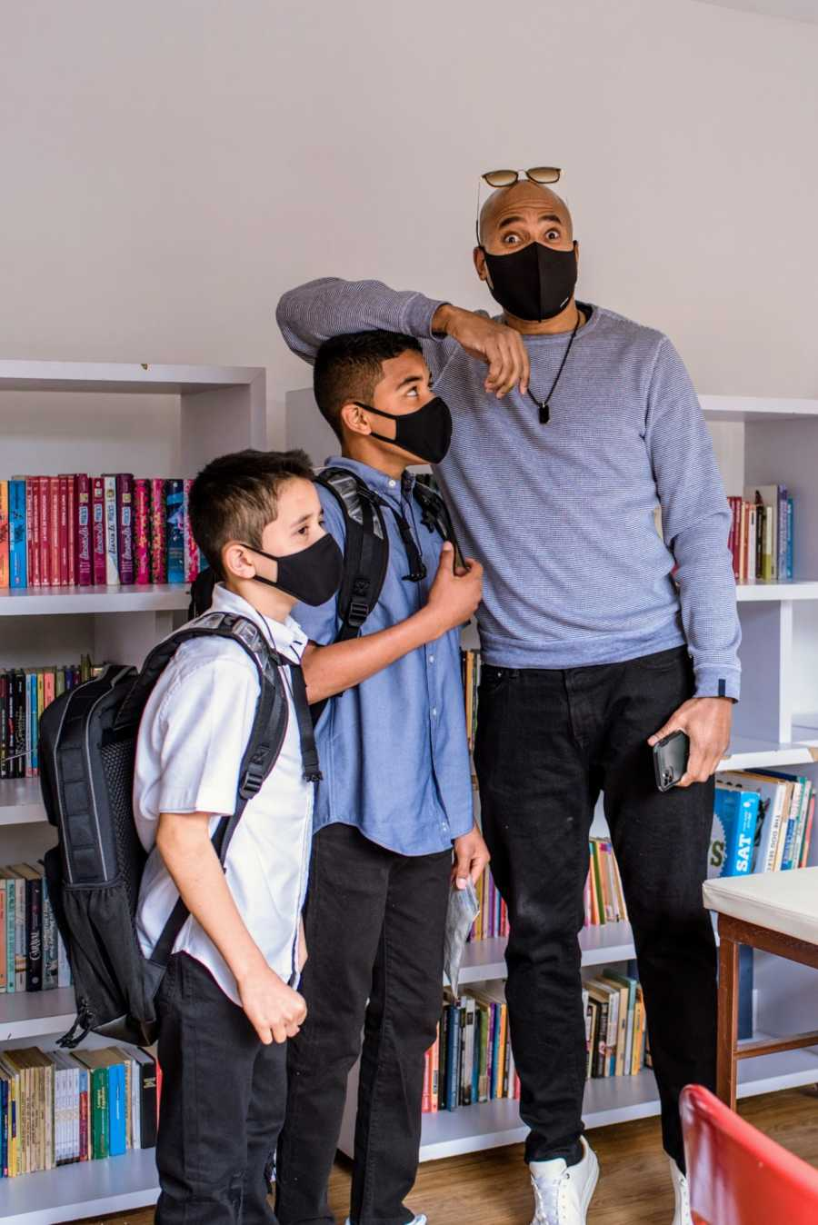 A pair of adopted brothers and their father stand by bookshelves