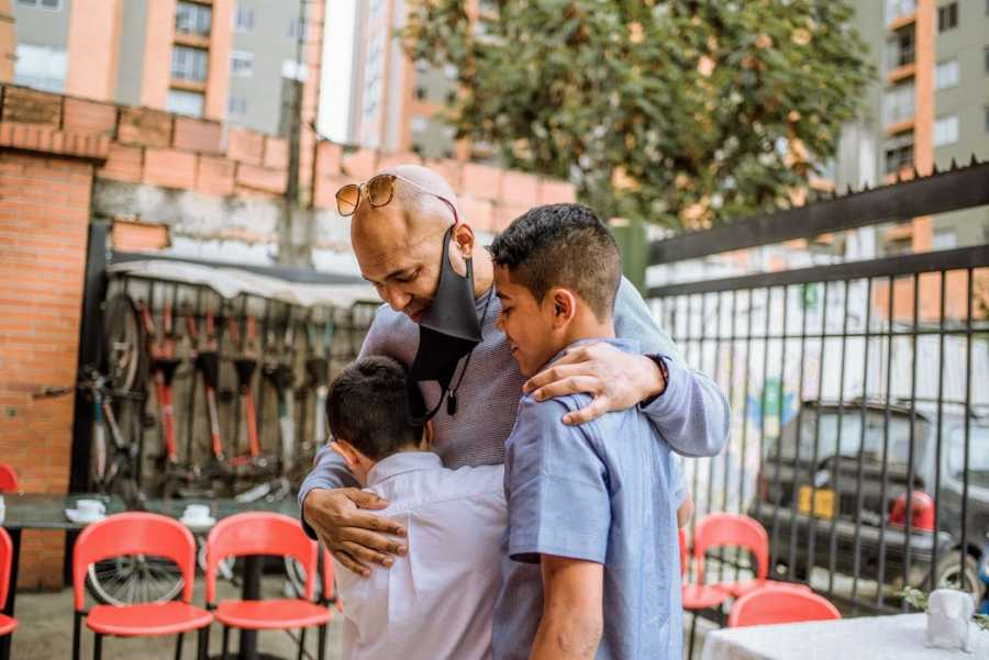 A single adoptive father hugs his sons when he meets them in person