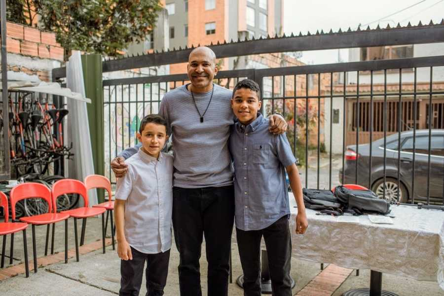 A single adoptive father and his sons stand together for a family photo