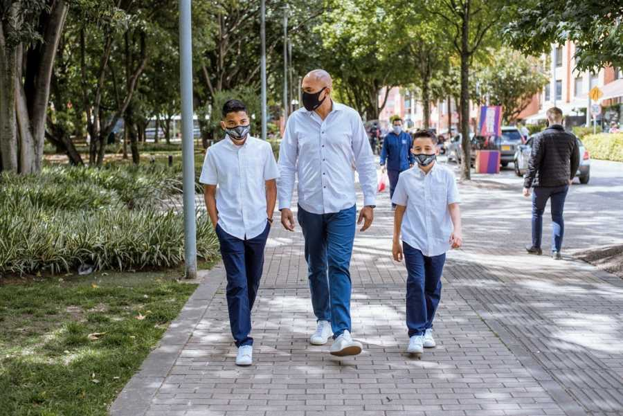 An adoptive father and his sons walk while wearing masks