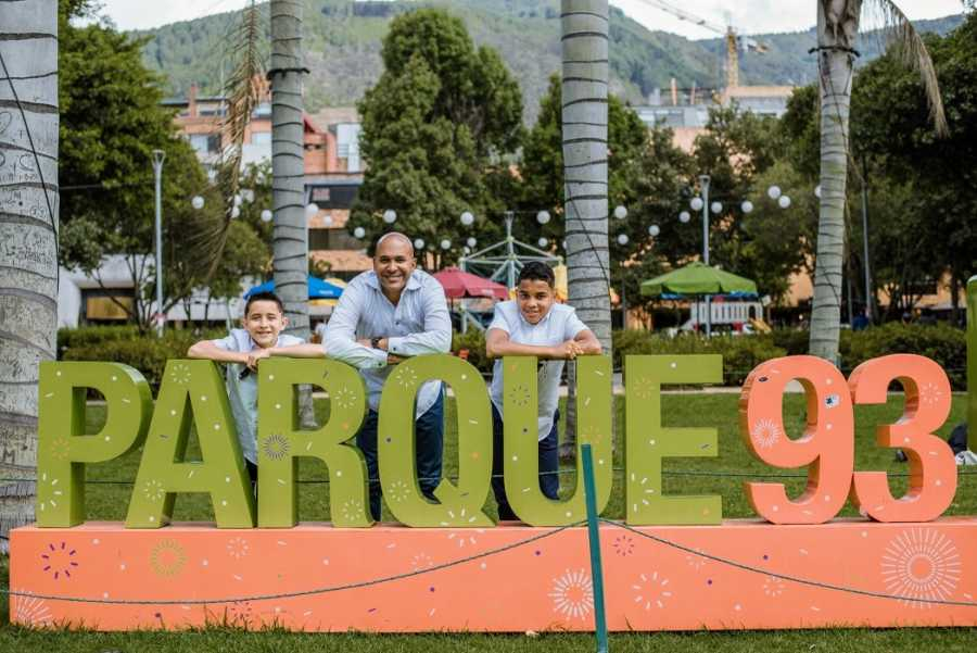 An adoptive father and his sons by a sign reading Parque 93