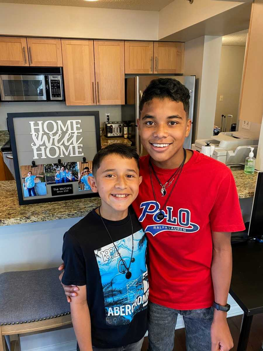 """A pair of adopted brothers stand in a kitchen by a """"Home Sweet Home"""" sign"""