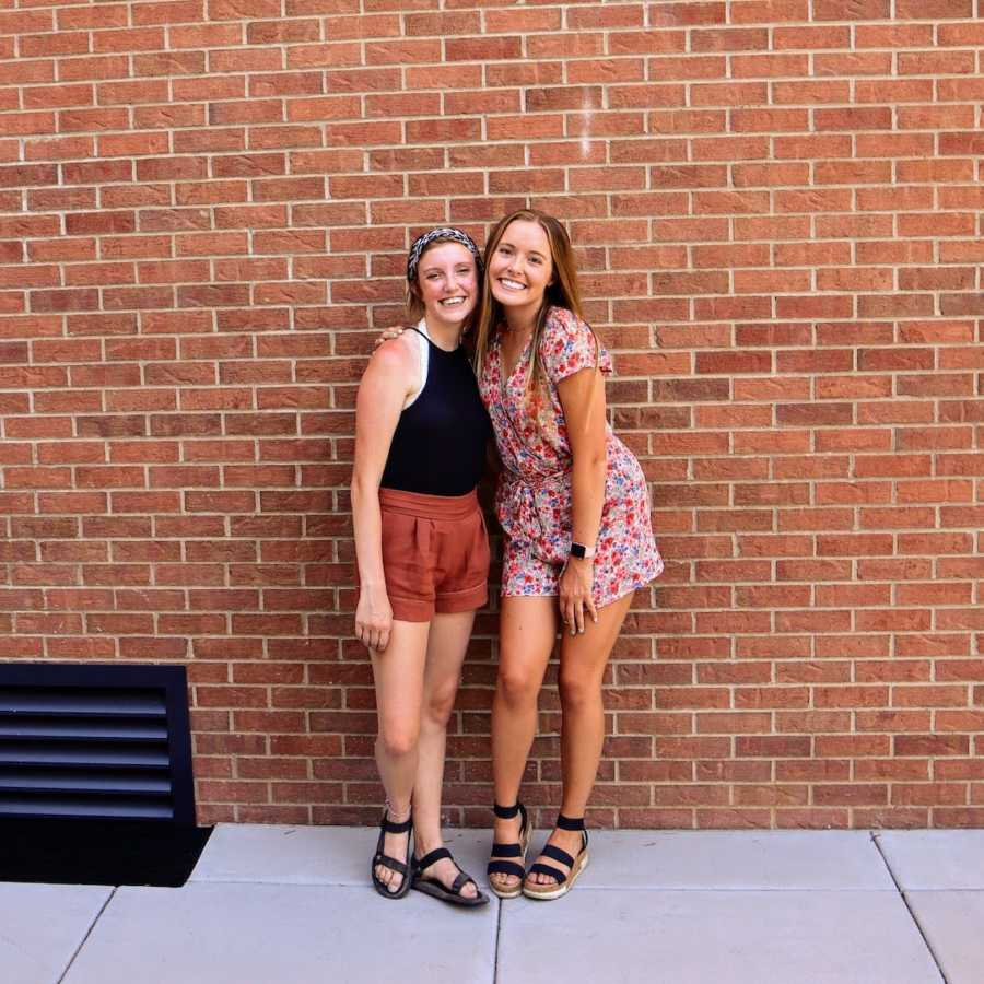Two friends standing in front of brick wall with arms around each other and smiling