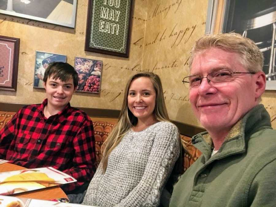 Son, daughter, and father sitting in a booth at restaurant smiling