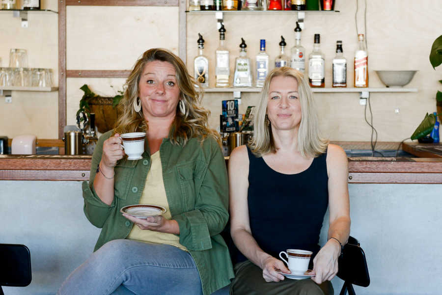 Two women sitting at the counter at a bar holding teacups