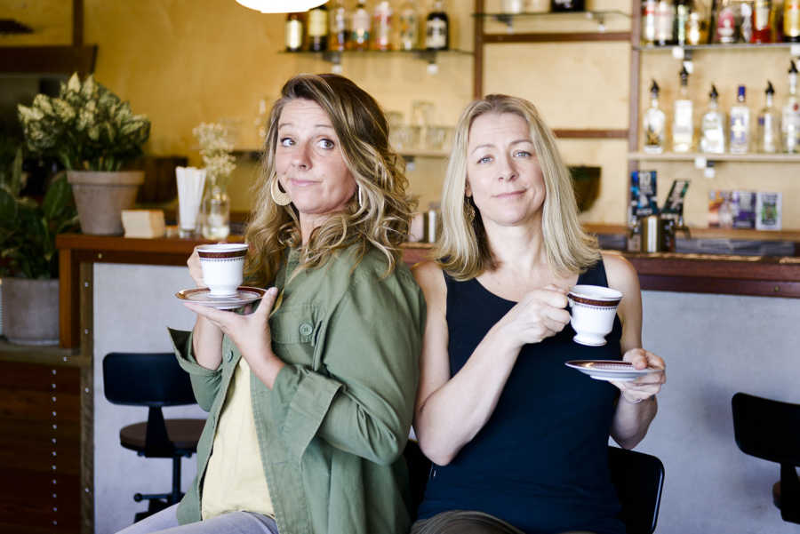 Two women at a bar holding teacups