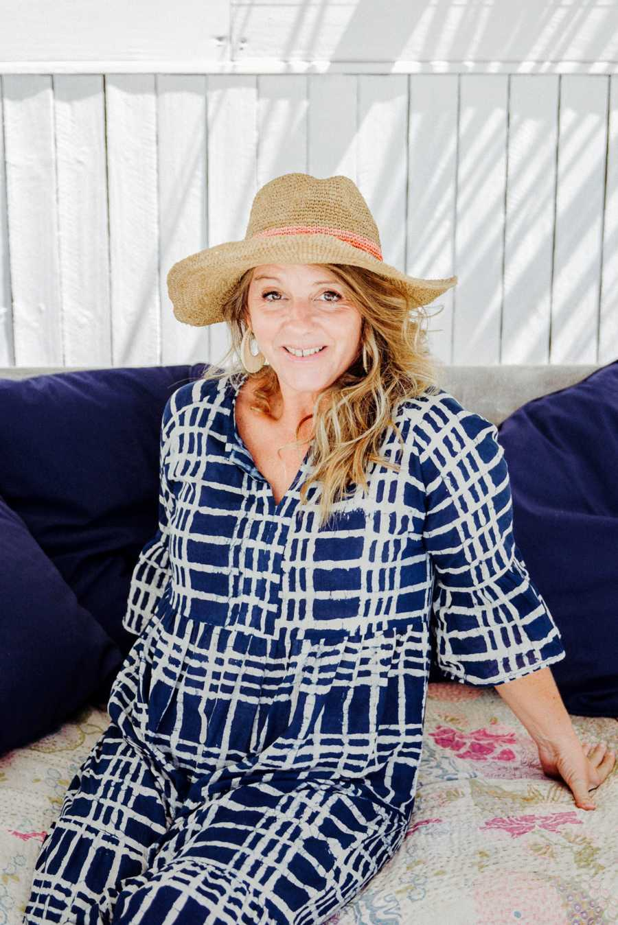 Woman wearing sunhat sitting on couch outside