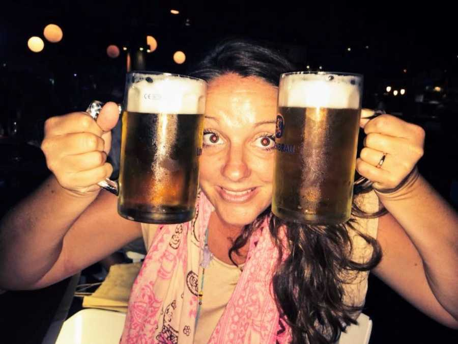 Woman at bar holding up two pints of beer