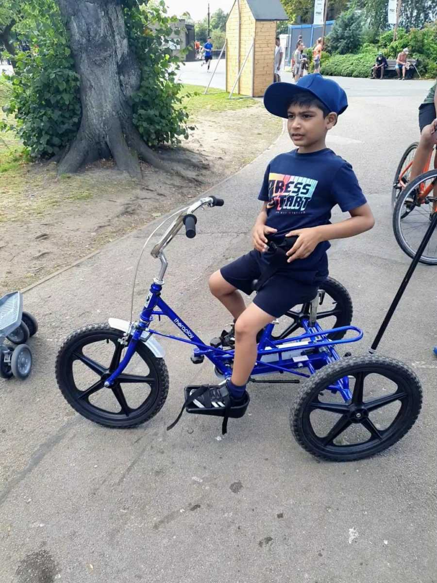 A boy with nonverbal autism on a three-wheeled bike