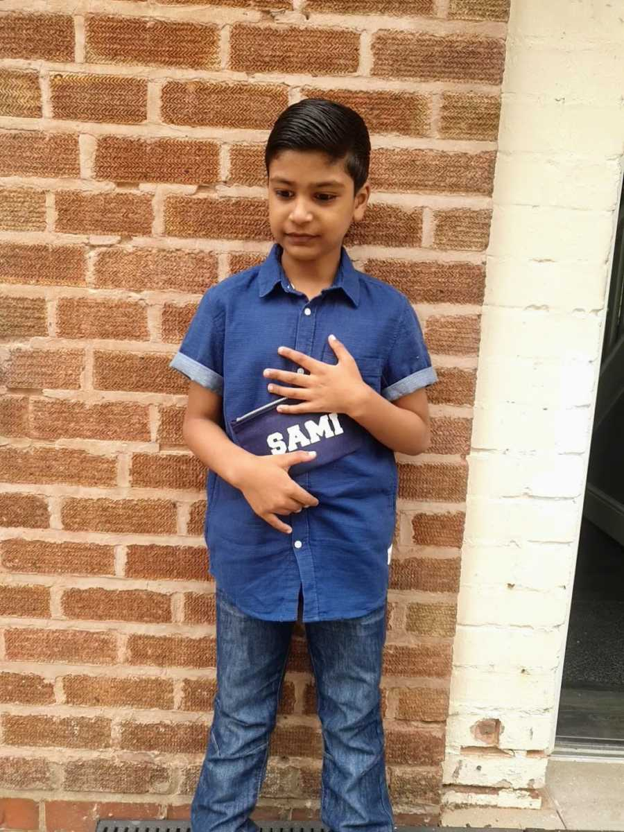 A boy with nonverbal autism stands against a wall holding a nametag
