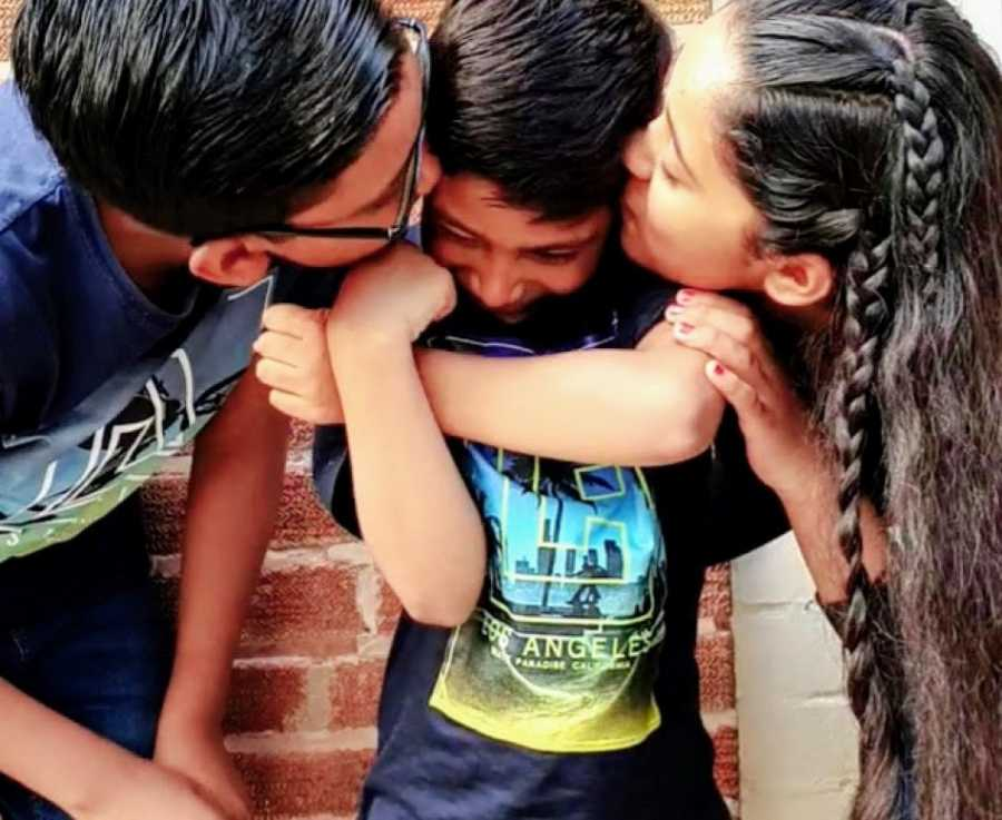 A boy with nonverbal autism is kissed by his siblings