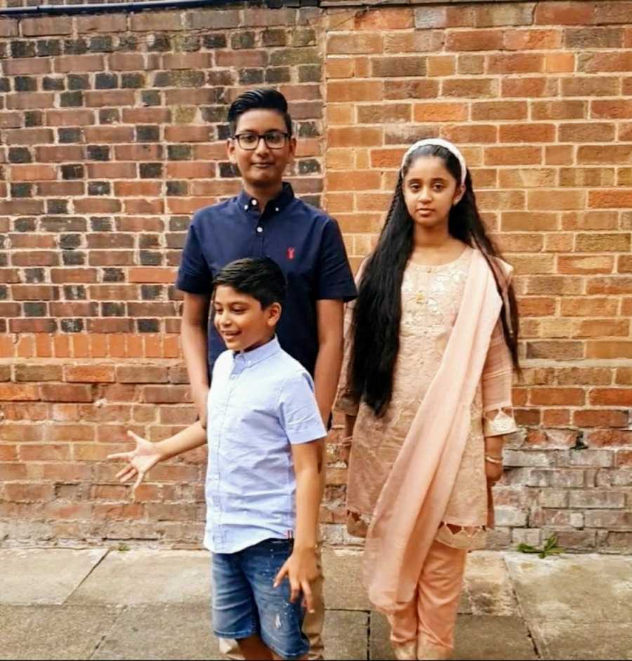 A boy with nonverbal autism stands with his siblings