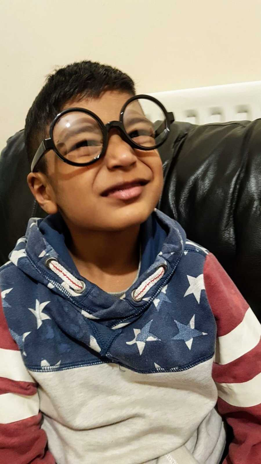 A boy with nonverbal autism wearing large glasses