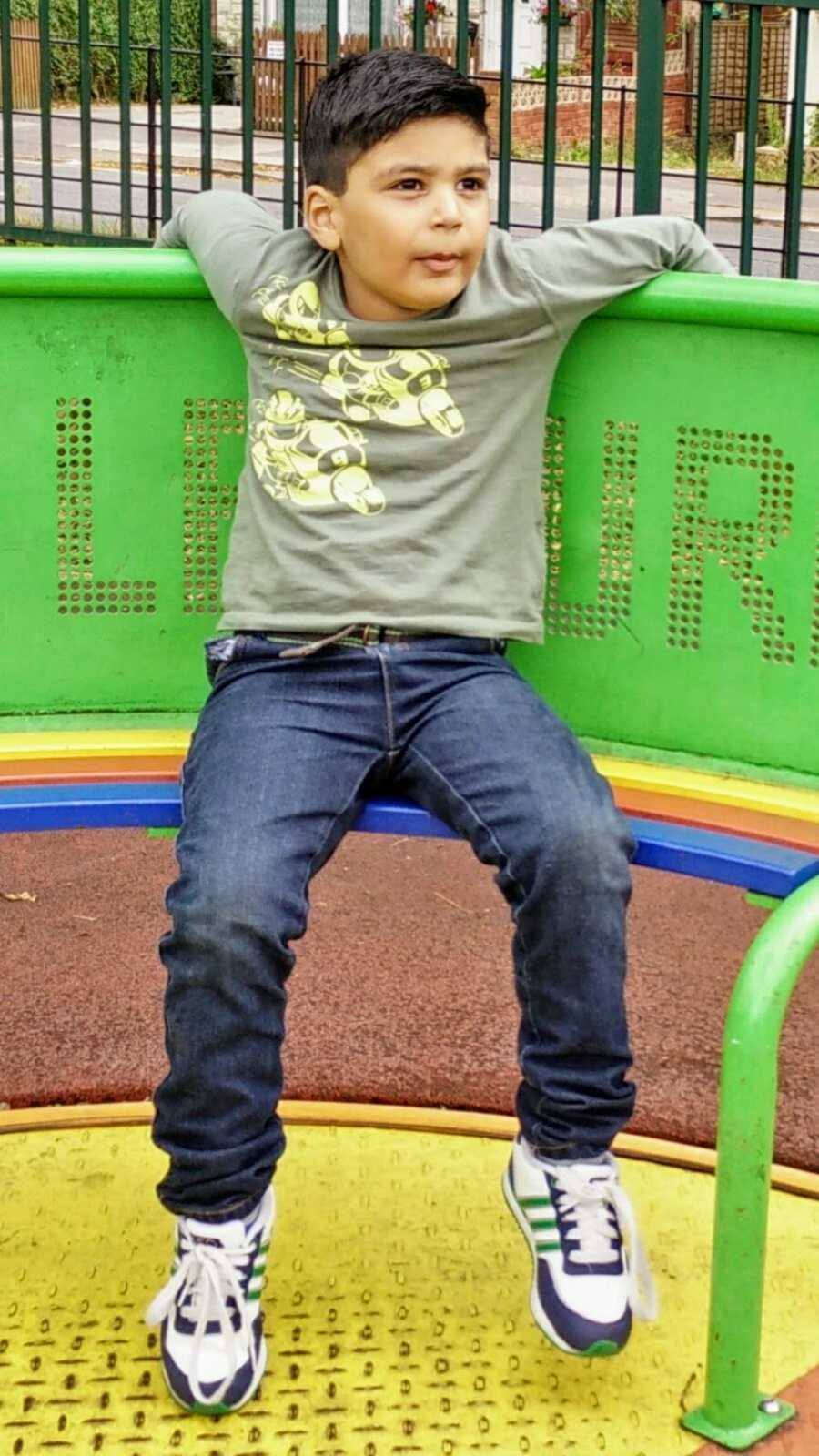 A boy with nonverbal autism sits on a playground