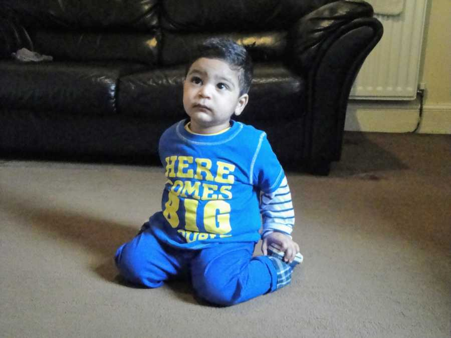 A toddler with nonverbal autism sits on the floor