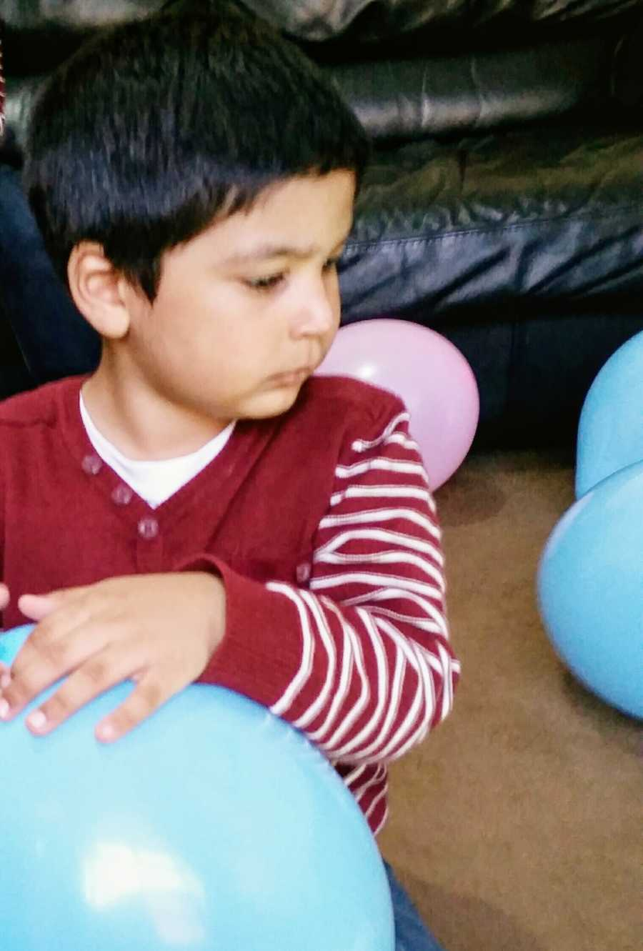 A toddler with nonverbal autism holds a balloon