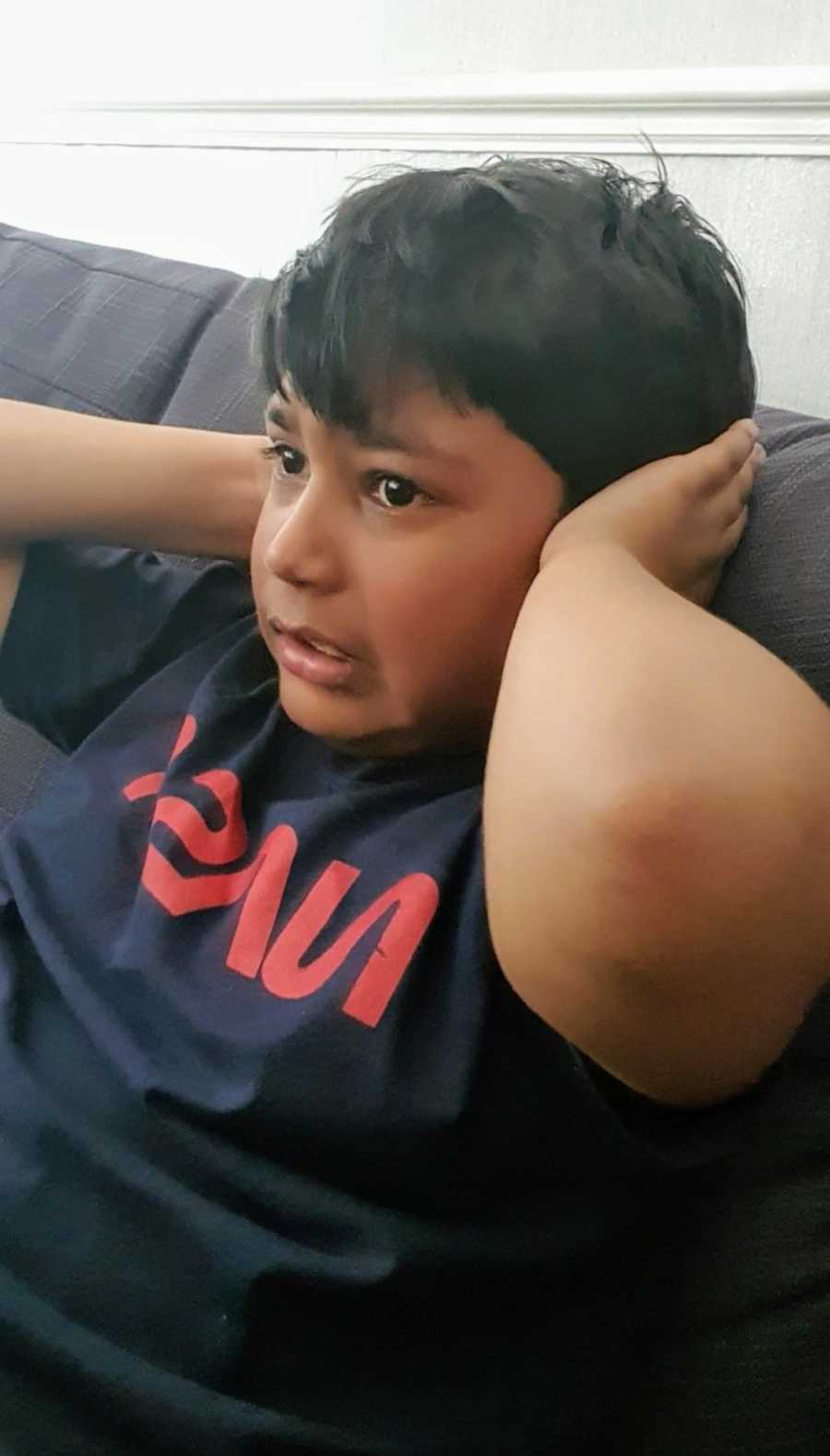 A boy with nonverbal autism covers his ears