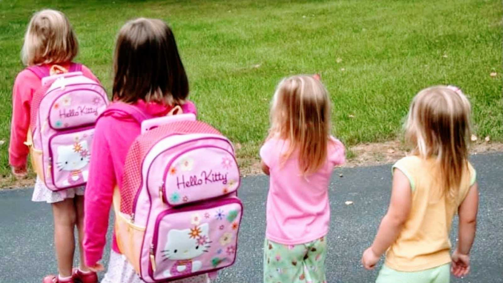 Mom snaps a photo of her four daughters as they walk to the bus stop for school