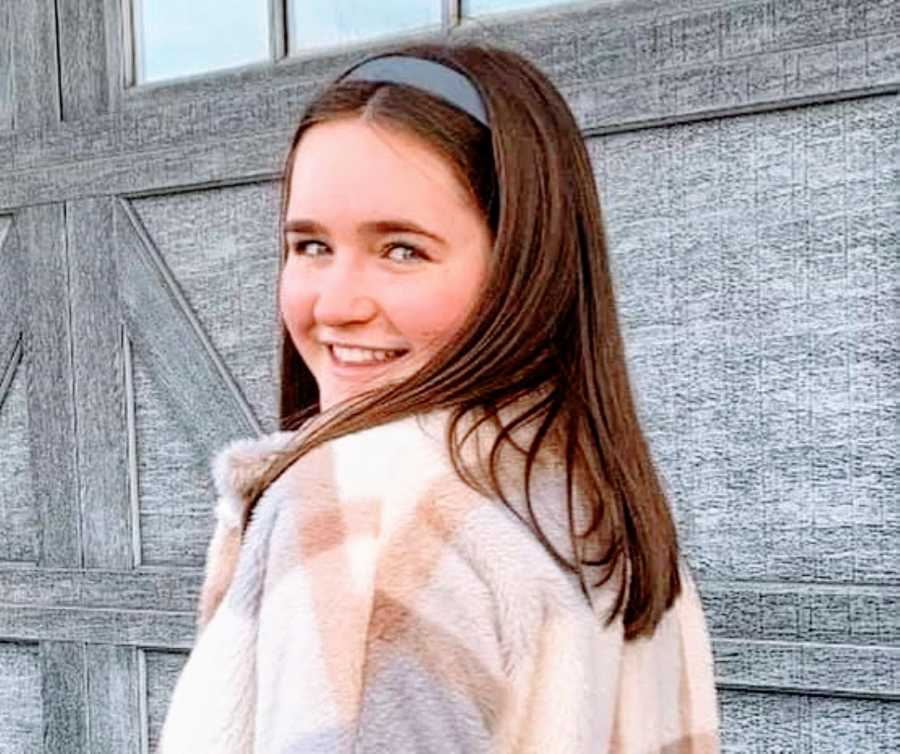 Young girl with gray headband and patterned jacket smiles at the camera