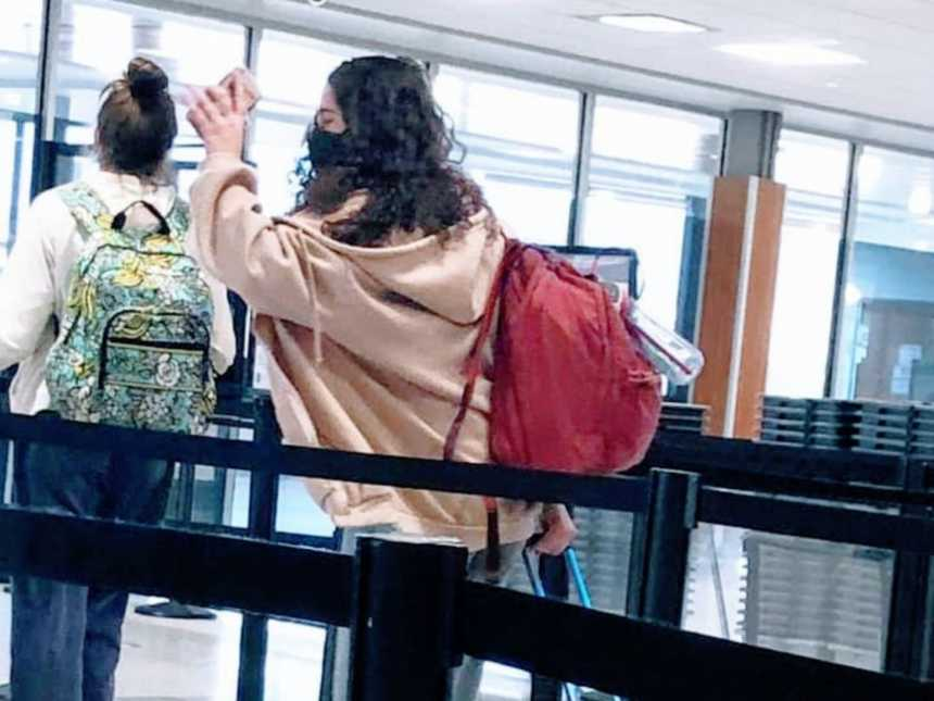 Daughter with a pink hoodie waves bye to her mom as she leaves to get on a plane