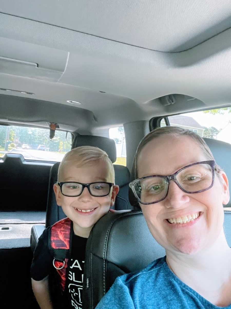 Woman takes a car selfie with her son, both wearing glasses