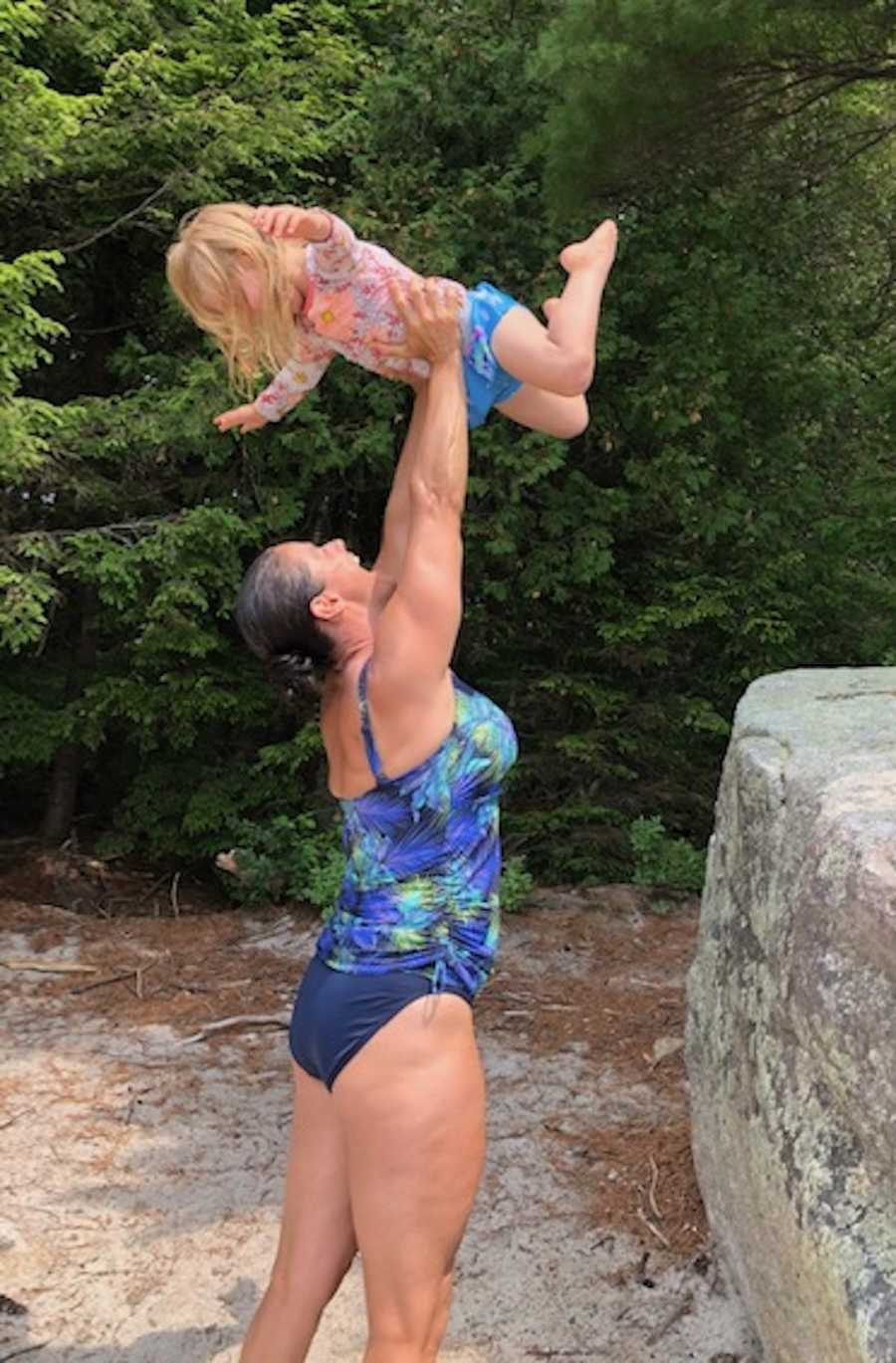 woman in bathing suit holding her kid up